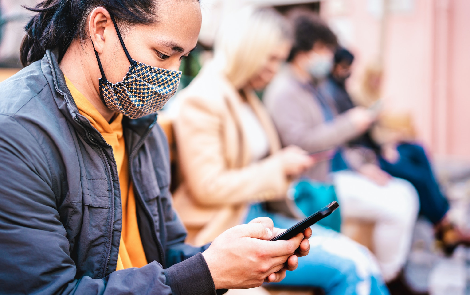 Asian guy using smart phone covered by face mask on Covid second wave